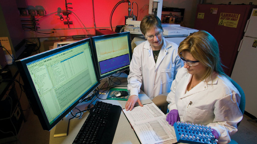 Two Scientists Reviewing Controlled & Uncontrolled Documents On A Computer